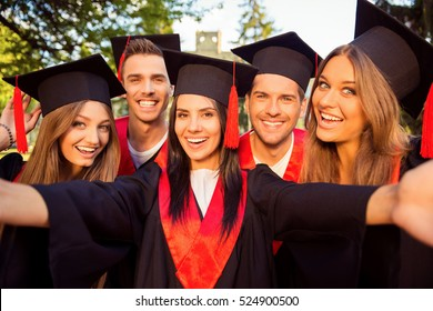 excited five successful happy five graduates in robes and hats with tassel together making selfie photo.