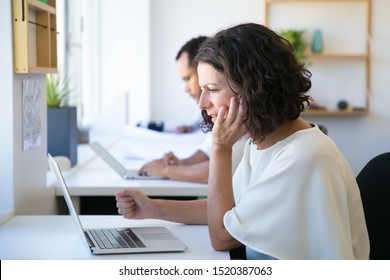 Excited focused female employee staring at computer monitor. Middle aged Caucasian woman sitting at workplace, using laptop, looking at screen, reading carefully. Important email concept