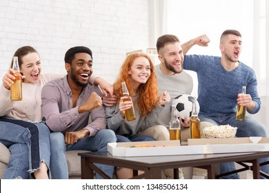 Excited football fans watching soccer on tv and drinking beer at home