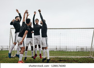 Excited football players jumping in excitement standing in a huddle near the goalpost. Players cheering and pepping themselves up before the start of a match.