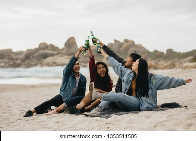 Excited four asian friends toasting beer on the beach. Young people on the beach having a party with drinks.