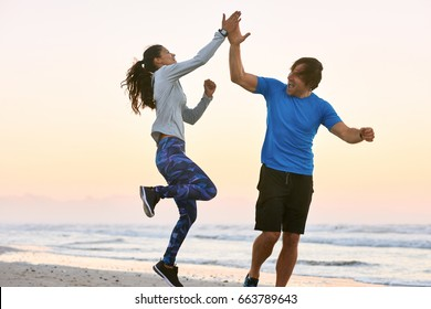 Excited friends couple high five jump in celebration after training their gruelling exercise workout run