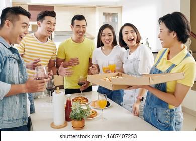 Aufgeregte Freunde, die sich in den Händen einer jungen Frau eine Schachtel frischer, heißer Pizza anschauen
