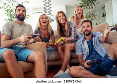 Excited friends playing video games at home, sitting on sofa and enjoying together.