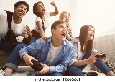 Excited friends playing video games at home and having fun