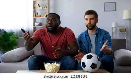 Excited friends watching football match, frustrated by defeat of favourite team
