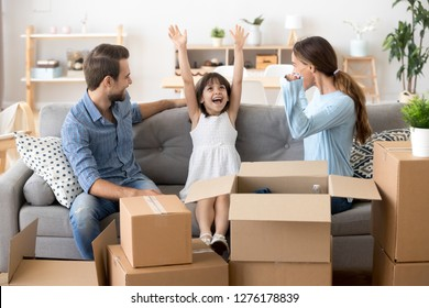 Excited funny kid girl feeling happy on moving day, cheerful cute child daughter enjoying family relocation to new modern home apartment sitting on sofa in living room with mom dad unpacking boxes