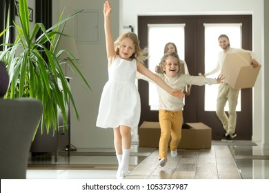 Excited funny kids boy and girl running inside luxury big modern house on moving day, cute children entering exploring new home, happy young family buying real estate, mortgage and relocation concept