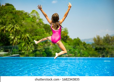 Excited funny little girl jumping to the swimming pool. Happy summer vacation