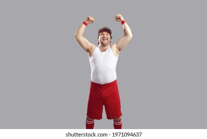 Excited funny overweight sportsman in sportswear showing power standing with raised fist a looking up. Portrait of self assured guy threaten heaven isolated on grey studio copy space background