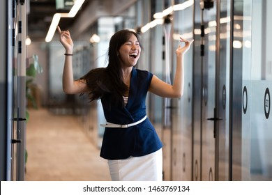 Excited funny young asian business woman celebrate success in victory dance, happy euphoric proud chinese female professional winner feel overjoyed by corporate reward standing in office corridor