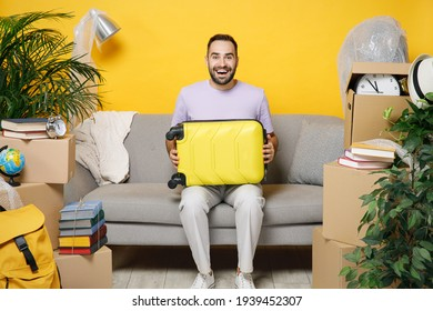 Excited funny young owner man hold suitcase sits in living room on sofa at home household unpacking stuff indoor plant rents flat isolated on yellow wall. Relocation moving in new apartment concept