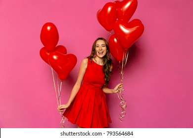 Excited funny young woman celebrating Valentine's day, holds red balloons in form of hearts in two hands. Dressed in red dress, with curly long hair.