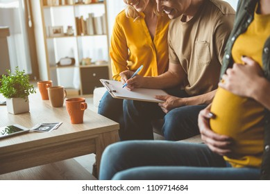 Excited future parents are signing a contract with surrogate expectant mother. They are sitting on sofa and smiling with happiness