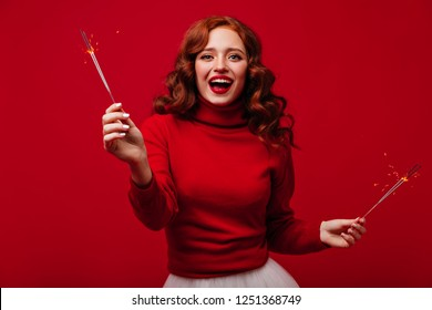 Excited ginger woman with sparklers laughing on red background. Indoor photo of ecstatic long-haired girl dancing in new year with bengal lights.