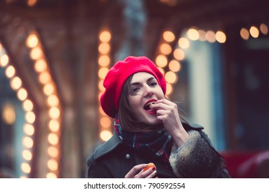 Excited girl in amusement park in winter day. Outdoor photo of happy woman with brown hair eating tangerine and posing in front of carousel.