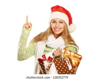 Excited girl with bag full of xmas gifts and demonstrating something in her hand isolated on white background.