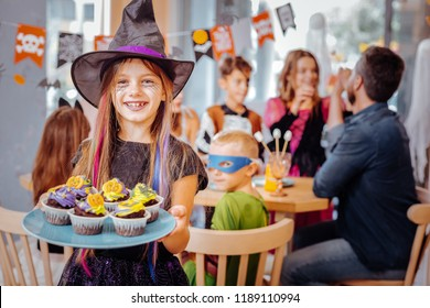 Excited girl. Beaming happy girl wearing Halloween suit feeling excited holding plate with bright cupcakes