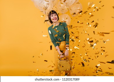 Excited girl with black hair dancing under sparkle confetti. Studio shot of carefree female model fooling around in her birthday and posing on yellow background.