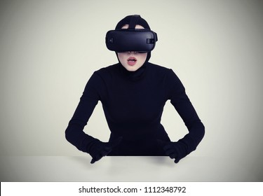 An excited girl in a black suit wears VR headset to experience the new technoligies of vitrual reality. Hi-Tech gadgets for geeks and technical enthusiasts. Virtual reality helmet for entertainment.