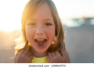 Excited girl child laughing while looking at camera