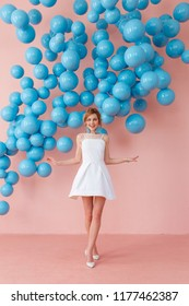 Excited girl in cute white dress dancing with smile on pink wall background decorated with blue balls.