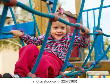 Excited girl developing dexterity at playground in summer day