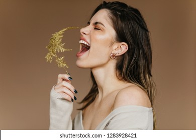 Excited girl in earrings posing with flower. Inspired brunette young lady laughing during shooting.