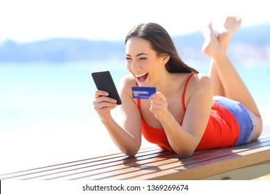 Excited girl finding ecommerce offers buying online with phone and credit card on the beach