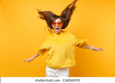 Excited girl in fur sweater and heart orange glasses fooling around in studio jump with flying hair isolated on bright yellow background. People sincere emotions, lifestyle concept. Advertising area