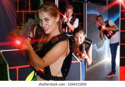 Excited girl holding laser pistol while playing lasertag game with friends in dark labyrinth