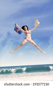 Excited girl jumping at a beautiful beach while holding a bag and hat
