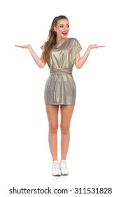 Excited Girl Presenting Product. Smiling young woman in gold mini dress and white sneakers standing with open hands raised and looking. Full length studio shot isolated on white.