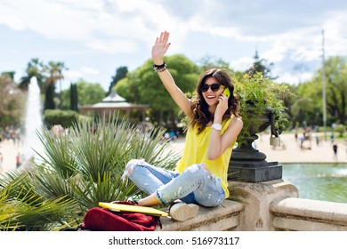 Excited girl in sunglasses is sitting on fence in summer park. She is speaking on phone and looking far away.