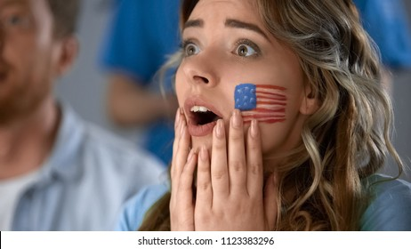 Excited girl watching American football, worrying about defeat of favorite team