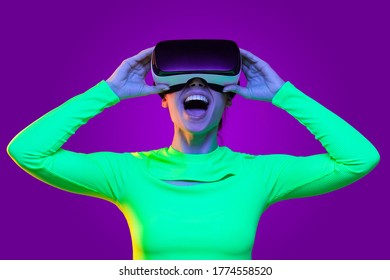 Excited girl wearing virtual reality headset, feeling amazed by VR techonology, isolated on neon purple background