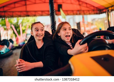 Excited girlfriends in amusement park driving bumper car