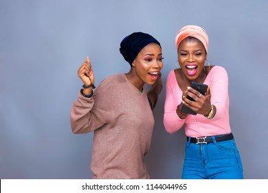 excited girls looking at a phone. young black girls very excited while holding and looking at a phone.
