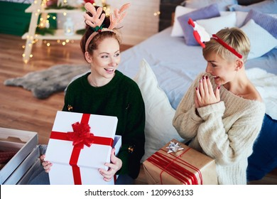 Excited girls opening christmas gift