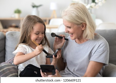 Excited grandmother and granddaughter have fun sitting on couch playing together, happy granny and grandchild do girly things putting make up on faces and laughing, cute girl smiling painting grandma