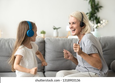 Excited grandmother with granddaughter in headphones listen to music, dancing, having fun at home, smiling grandma with preschool grandchild hearing songs in headset, playing together