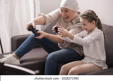 excited grandmother and granddaughter playing with joysticks, cancer concept