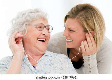 Excited grandmother listening music together with her granddaughter at home