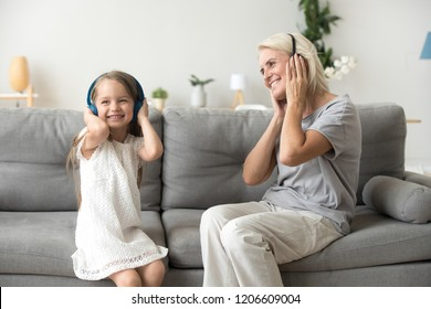 Excited grandmother and smiling little granddaughter listen to music in headphone, grandma and grandchild have fun relaxing on couch at home together, granny enjoy spending time with young generation