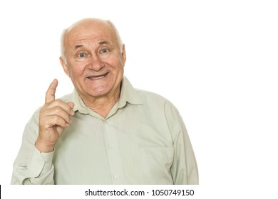 Excited grandpa posing on white background. Happy senior man smiling joyfully holding up his finger having an idea copyspace inspiration concept.