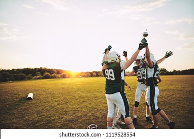 Excited group of American football players standing together in a huddle and raising a championship trophy in celebration