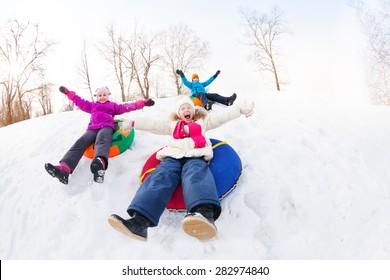 Excited group of children sliding down on tubes