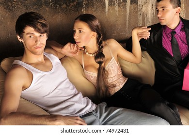 Excited group of people at nightclub sitting on sofa