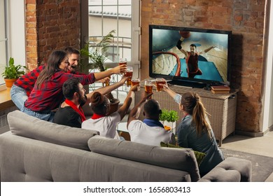 Excited group of people watching basketball sport match at home. Multiethnic group of emotional friend, fans cheering for favourite national team, drinking beer. Concept of emotions, support.