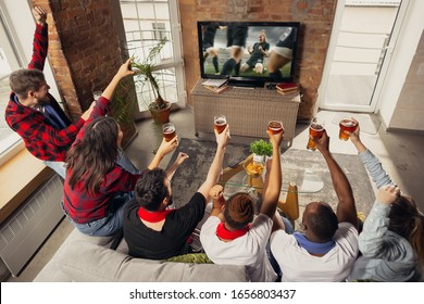 Excited group of people watching football, soccer sport match at home. Multiethnic group of emotional friend, fans cheering for favourite national team, drinking beer. Concept of emotions, support.